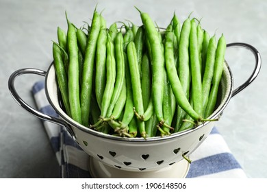 Fresh green beans in colander on light table, closeup