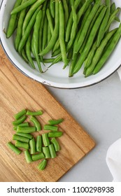 Fresh Green Beans on a Wooden Cutting Board; Cut; Against a Gray Background