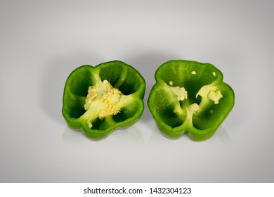 Fresh green bell peppers (capsicum) from top view. These capsicum are sliced and on white background