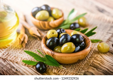Fresh green and black olives in bowl on old table. Olive oil in bottle background.