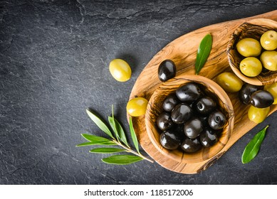 Fresh green and black olives on dark stone table or board. Olive leaves, wooden pickers on black blackground.