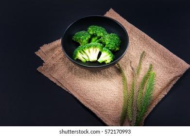 Fresh green broccoli in bowl on black background