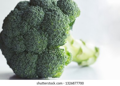 Fresh green broccoli with a stem on white background