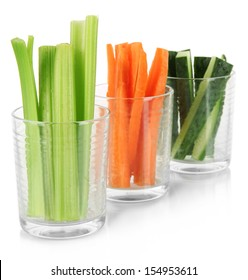 Fresh green celery with vegetables in glasses isolated on white