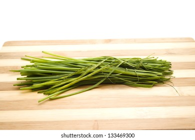 Fresh Green Chives on Wooden Plate
