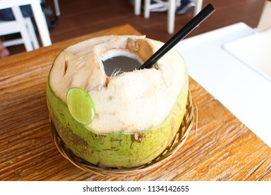 Fresh green coconut drink on the brown wooden table