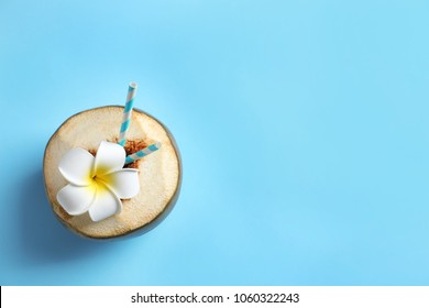Fresh green coconut with drinking straws and flower on color background