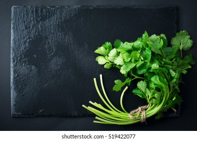 Fresh green coriander, coriander leaves on a black slate background. Selective focus.
