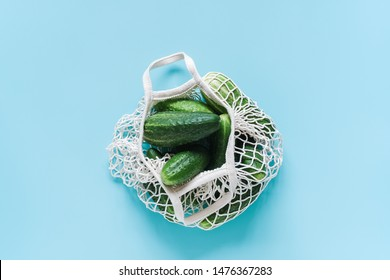 Fresh green cucumbers vegetables in reusable shopping eco-frendly mesh bag on blue background. Concept no plastic and zero waste. Copy space Top view Flat lay.