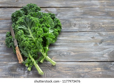 Fresh green curly kale leaves on a wooden table. selective focus. free space. rustic style. healthy vegetarian food