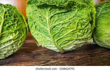 Fresh green garden cabbage on rustic wooden background.