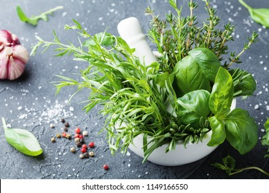 Fresh green garden herbs in mortar bowl and spices on black stone table. Thyme, rosemary, basil, and tarragon for cooking.