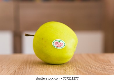Fresh green golden delicious apple with brand sticker on a wooden table in soft focus on August 2017 in Poznan, Poland