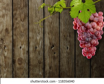 Fresh green grapes with leaves on wood background