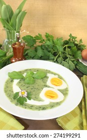 fresh green herbs soup with eggs and a dollop of cream