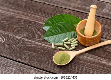 Fresh green Kratom leaf ( Mitragyna speciosa ) with kratom powder capsule isolated on wooden table background.