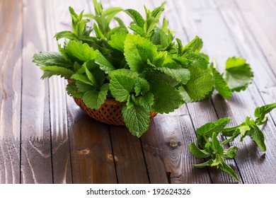 Fresh green leaves of melissa and peppermint in bowl on wooden background. Selective focus, horizontal.