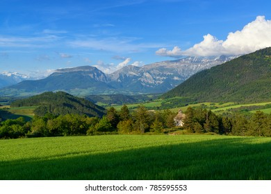 Fresh green meadow, little church and mountains. French rural evening landscape.
