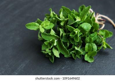 Fresh green mint on a black stone background