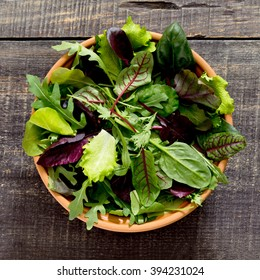 Fresh green mixed salad in a bowl on a dark wooden table