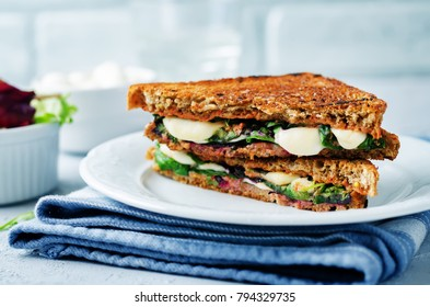 Fresh green mozzarella grilled rye sandwich on a stone background. toning. selective focus