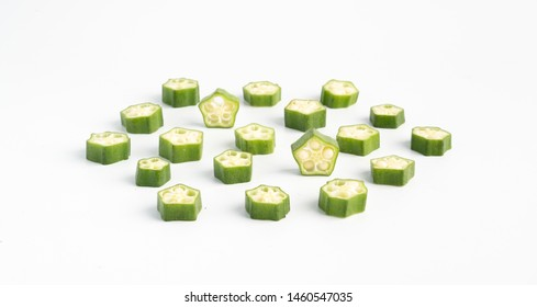 Fresh green okra cut into pieces in white background