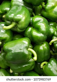 Fresh green organic bell peppers capsicum on display for sale at local farmer's market departmental store.