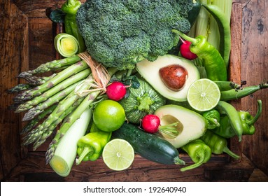 Fresh green organic vegetables on rustic dark wood background.Vegan food concept.