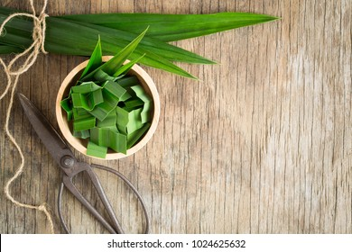 Fresh green pandan in a wooden bowl on wood table,pandan leaves on old wood background,top view and copy space