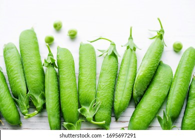 Fresh green pea pods on a white painted surface, top view