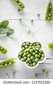 Fresh green peas on white table