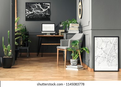 Fresh green plants in real photo of dark room interior with wainscoting on wall, grey armchair and wooden desk with empty screen computer