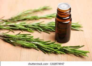 Fresh green rosemary branch and aroma oil bottle on wooden background. Concept aromatherapy, medicine.