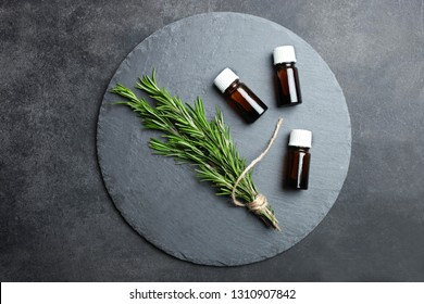 Fresh green rosemary branch and bottle of aroma oil on round slate board on black background. Concept aromatherapy, medicine. Top view.