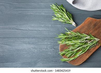 Fresh green rosemary on blue wooden background, flat lay. Space for text