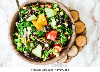 fresh green salad with avocado and corn in wooden plate on a light background,healthy lifestyle and raw food concept,top view