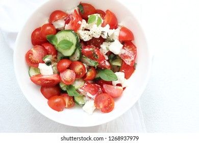 Fresh Green Salad of Cherry Tomatoes, Cucumber, Feta Cheese and Basil with Olive Oil on White Plate. Healthy Colorful Plant-based Summer Food.