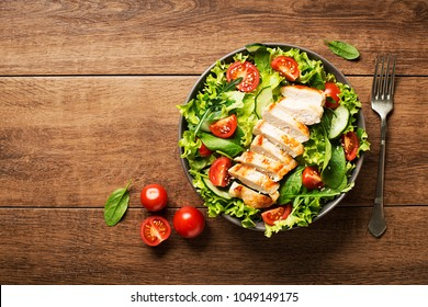 Fresh green salad with chicken breast and tomato.