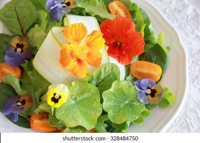 Fresh green salad with edible flowers in white serving dish, keto, ketogenic, low carb diet, sugar free, dairy free and  gluten free, healthy plant based vegan food