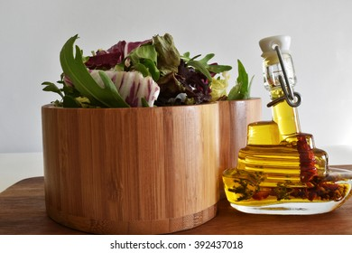 Fresh green salad mix in bowl and olive oil on wooden.