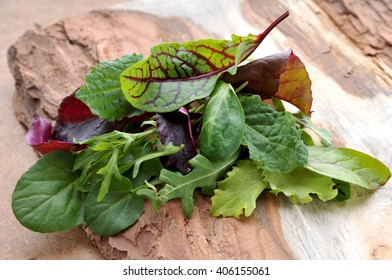 Fresh green salad mix on wooden tray.