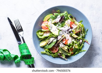 Fresh green salad with mixed green leaves, tomatoes and avocado with yogurt sauce and sesame. Low-calorie and weight less food.