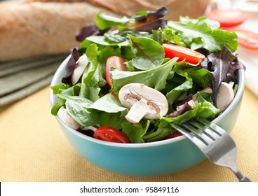 Fresh green salad with mushrooms, tomatoes and bread in the background.
