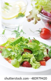 Fresh green salad with ripe tomatoes, pods of green peas and slices of strawberry.