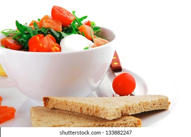fresh green salad with smoked salmon in white bowl