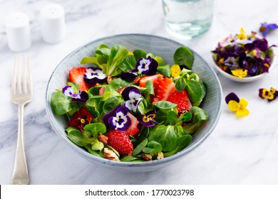 Fresh green salad with strawberries and edible flowers in a bowl. Marble background. Close up.