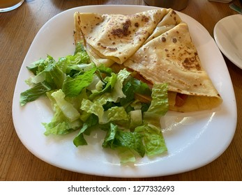 Fresh crêpe with green salat on the plate close up, pancake with a salat, healthy breakfast