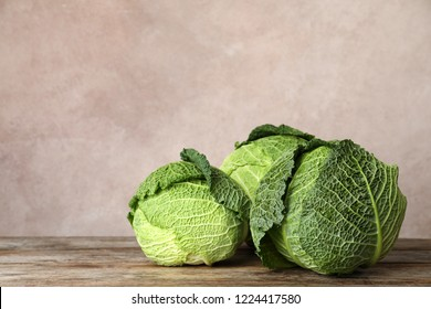 Fresh green savoy cabbages on wooden table. Space for text