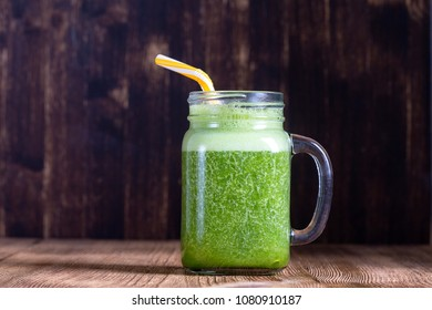 Fresh green smoothie from avocado, banana, parsley and honey in glass mug on wooden background, close up. Concept of healthy eating