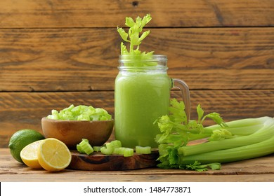 fresh green smoothie with celery apple and lime on rustic table background